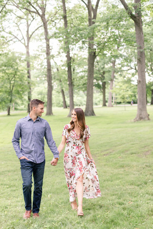 engaged cute couple walking holding hands at the Rivere Park Midland Michigan