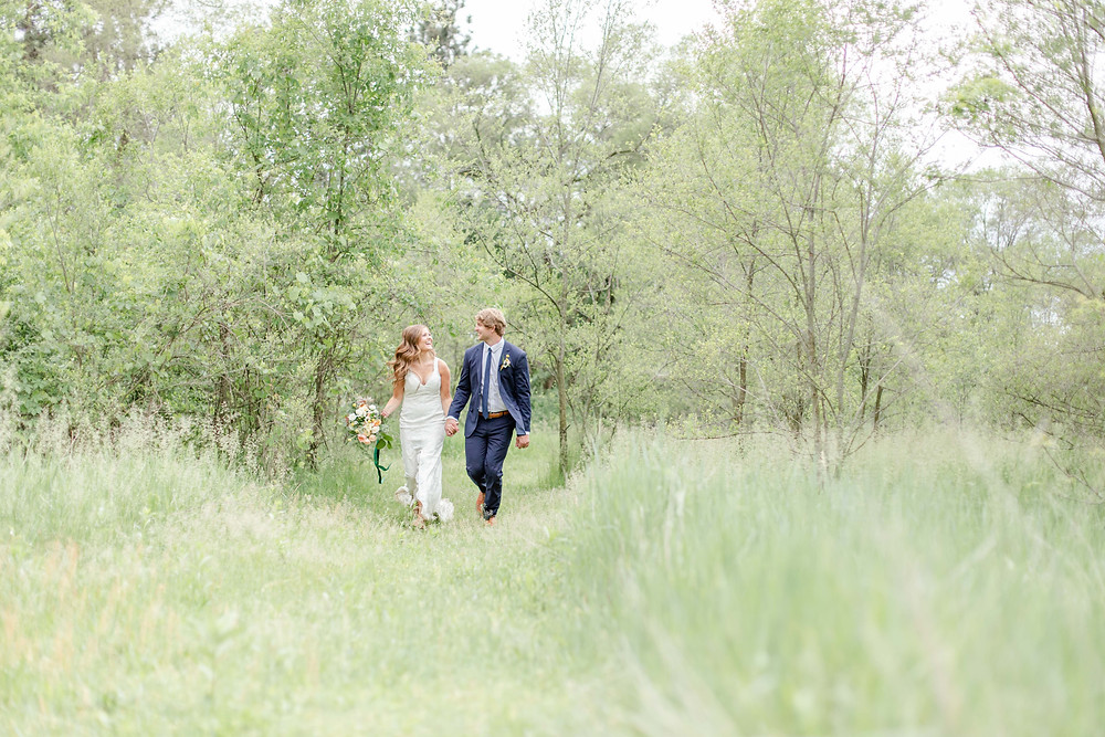 bride and groom walking in field smiling in the details byron center truer design