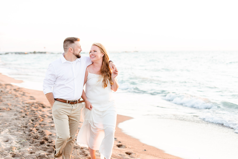 white dress engagement photos cute couple walking smiling on city beach new buffalo michigan