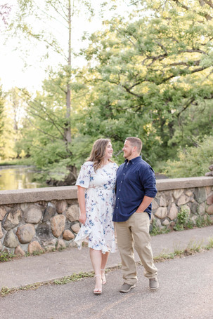 engagement photos cute couple walking on stone bridge at milham park kalamazoo michigan