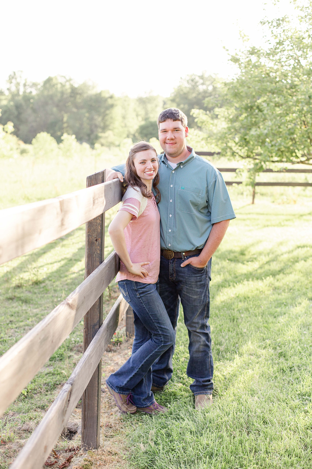 engaged couple standing along fence line Something Blue Berry Farm Wedding Venue