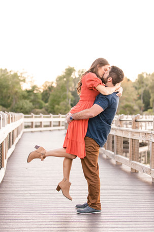 Cute couple kissing lifting on bridge Pickerel Lake Park Grand Rapids engagement session