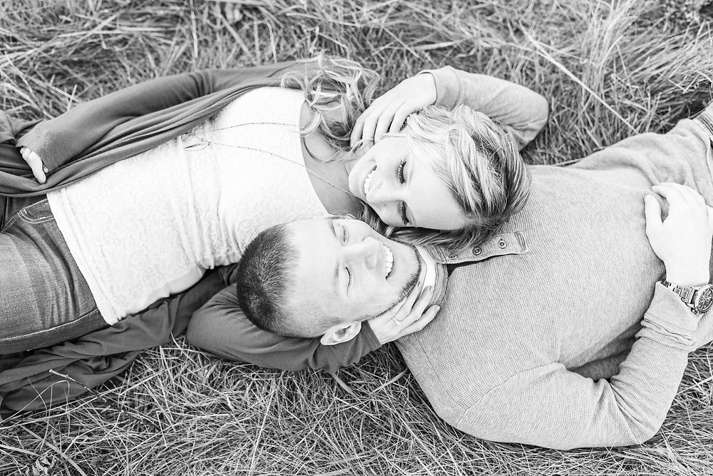 Josh and Andrea Photography engagement shoot Al Sabo cute couple smiling laying down in field