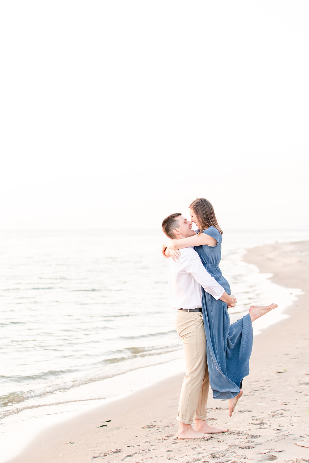 Josh and Andrea wedding photography husband and wife photographer team michigan engagement pictures session photo shoot fiance tunnel park lifting smiling beach