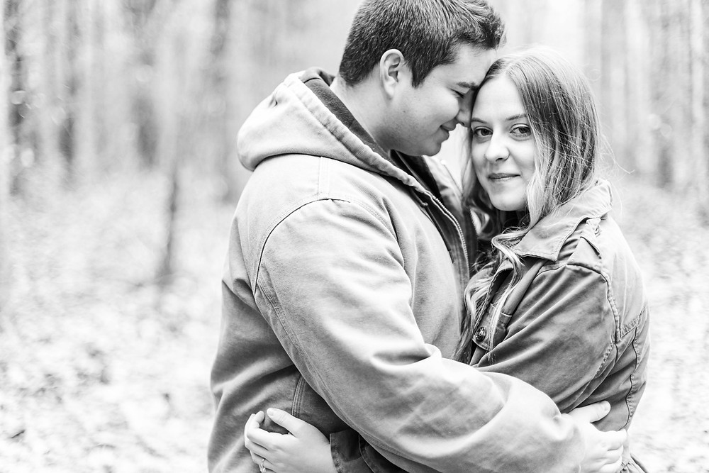 josh and Andrea photography husband and wife team michigan engagement photo shoot al sabo land preserve man and woman standing smiling in woods