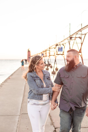 Engagement Photos Engaged Couple South Haven Beach Lighthouse Pier Michigan Engaged Couple walking on pier smiling