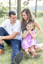 cute family sitting smiling on grass