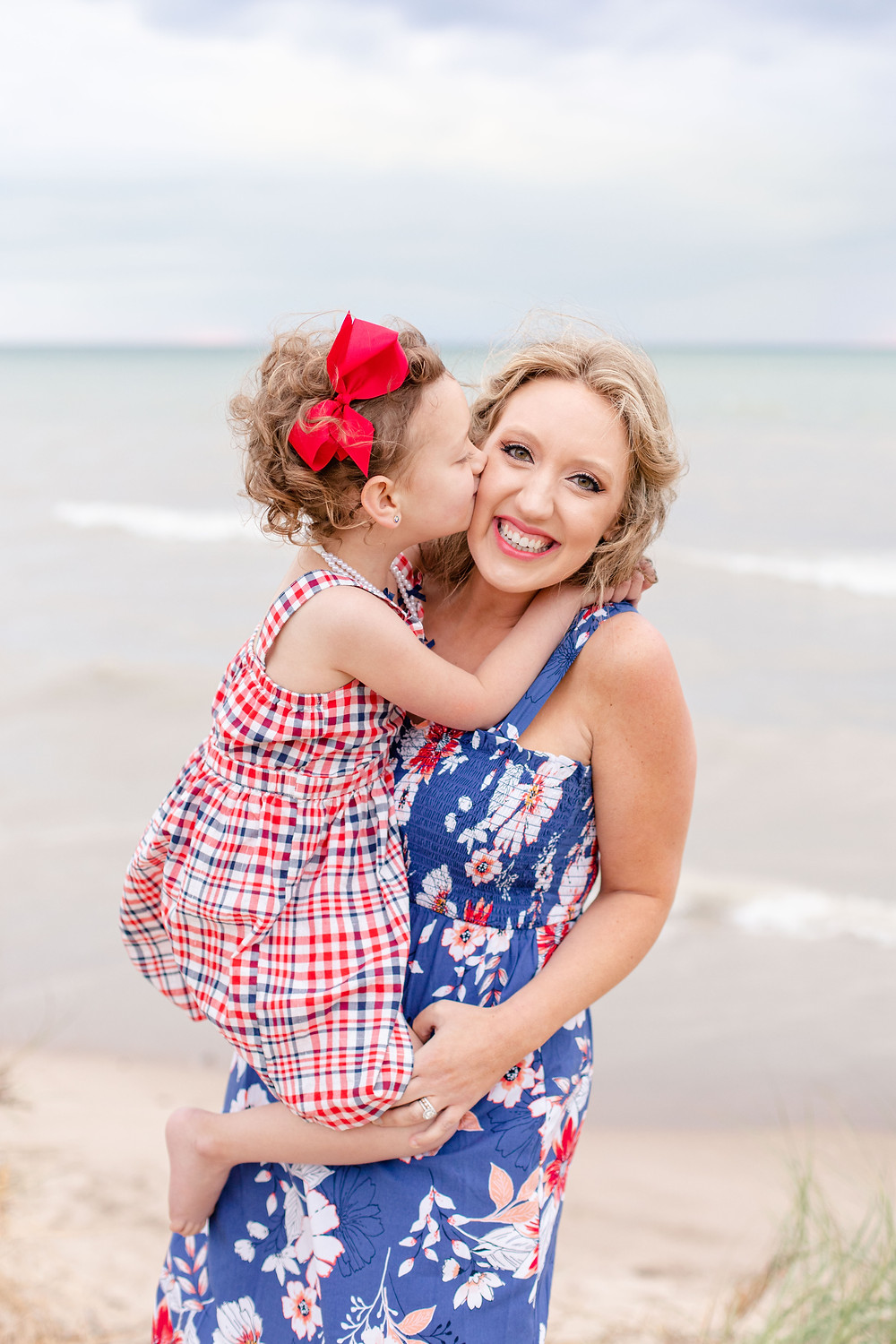 mom and daughter kissing on the beach Lake Michigan south haven family shoot red white and blue outfits
