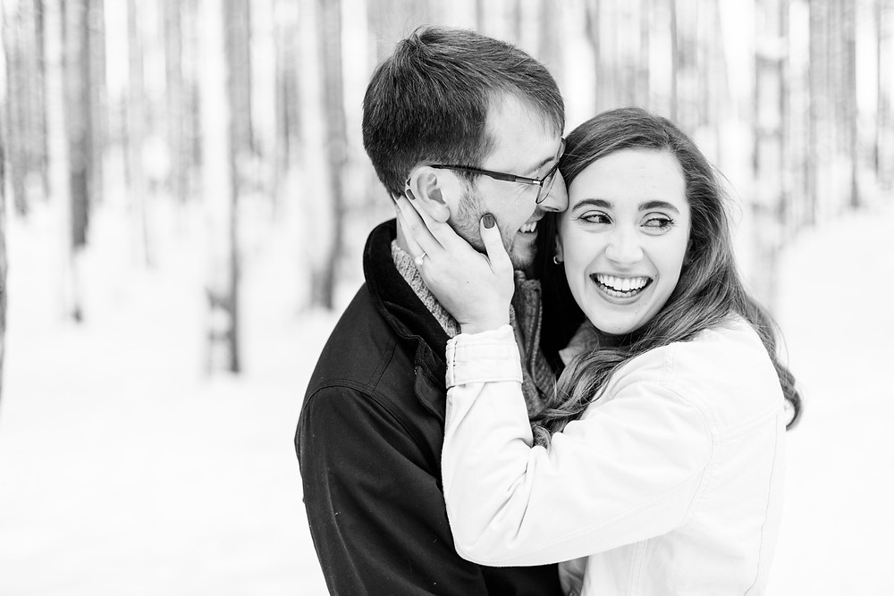 Josh and Andrea wedding photography husband and wife team michigan Grand Haven Rosy Mound engagement session fiance snowy forest woods smiling laughing