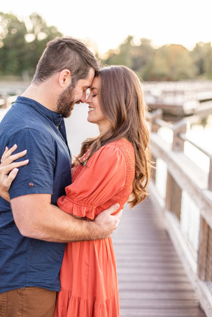 Cute couple smiling standing on the bridge Pickerel Lake Park Grand Rapids engagement session