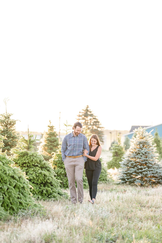 cute couple walking engagement photos Christmas tree farm