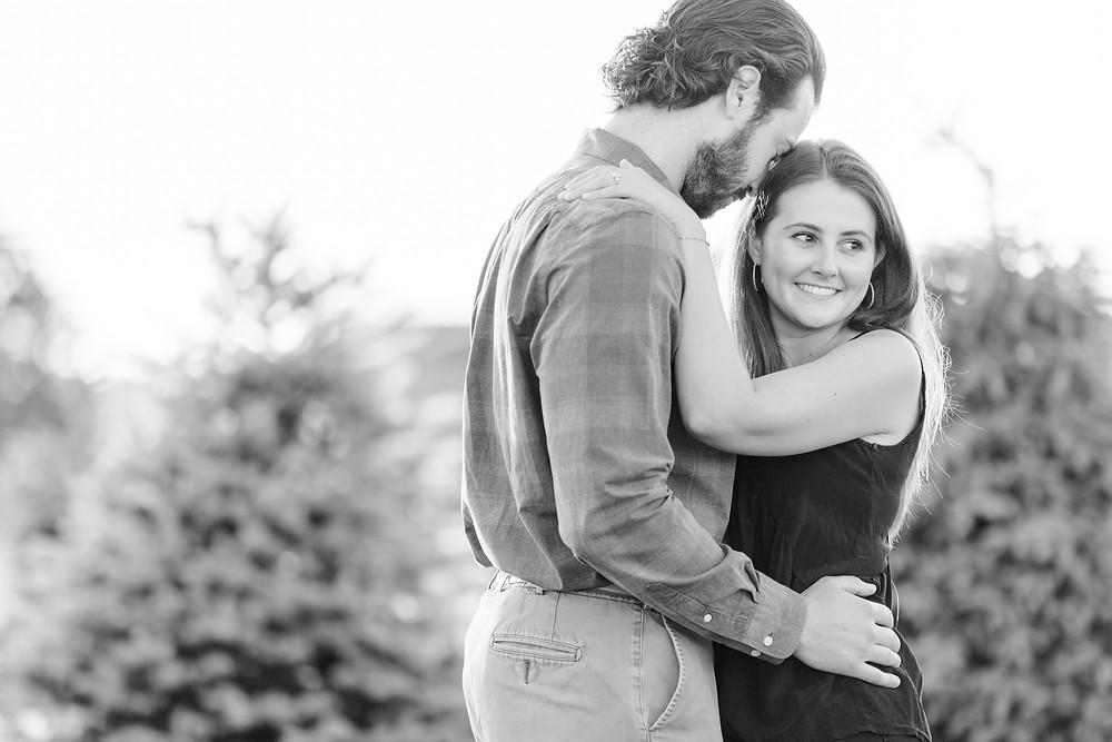 cute couple hugging engagement shoot Christmas tree farm