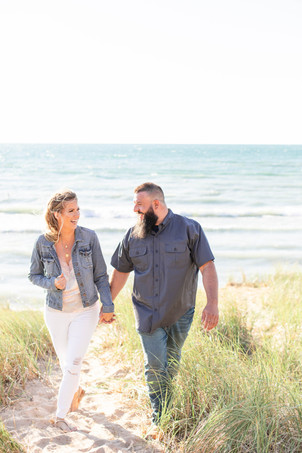 Engagement Photos South Haven Beach Michigan Engaged Couple walking in dune grass laughing