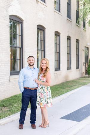 engagement photos couple standing in front of journeyman distillery weddings three oaks michigan