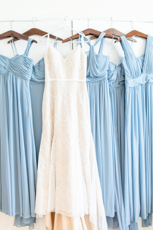wedding dress and bridesmaids dresses hanging up together dusty blue Kent Country Club Wedding Grand Rapids