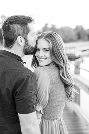 Cute couple smiling on bridge Pickerel Lake Park Grand Rapids engagement session