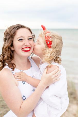 little girl kissing moms cheek on the beach Lake Michigan south haven family shoot