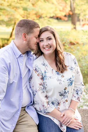 engagement photos cute couple sitting on bridge milham park kalamazoo michigan