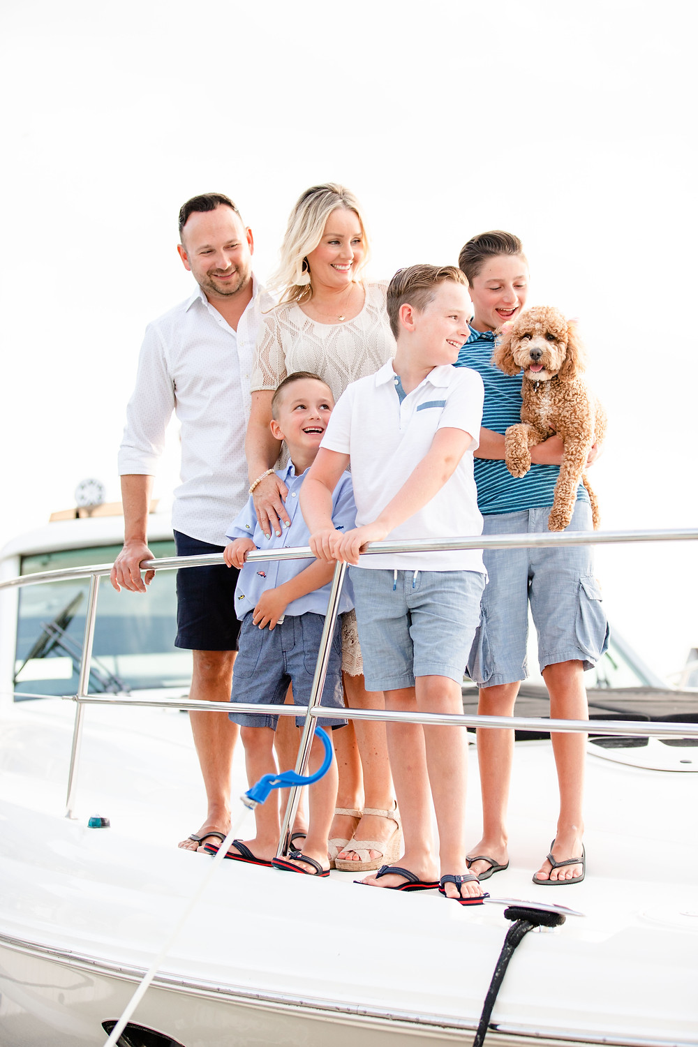 family of 5 photos standing laughing on bow of yacht boat new buffalo michigan