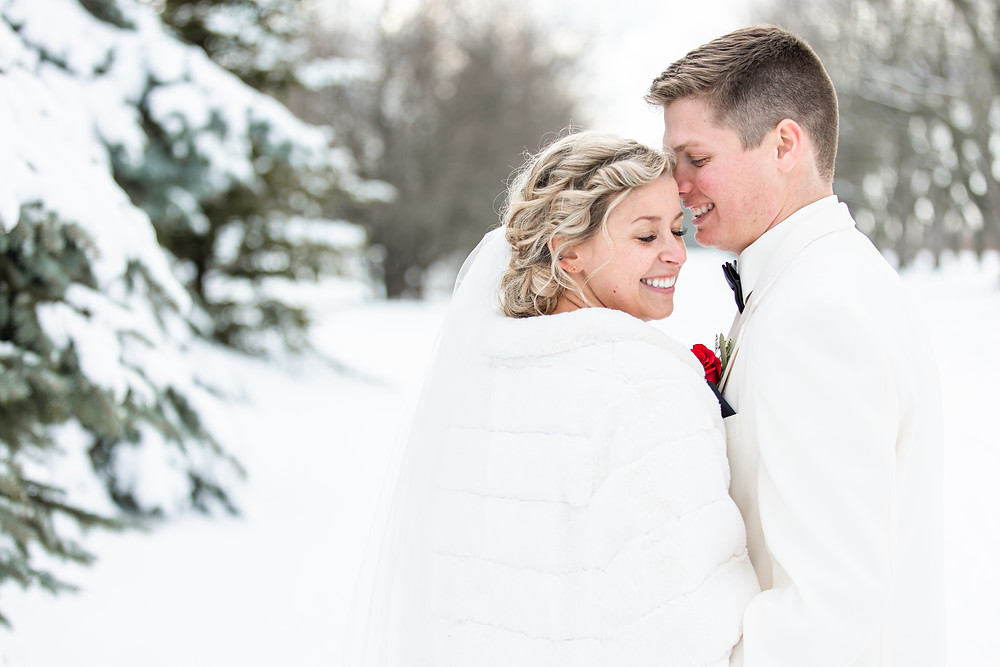 josh and Andrea photography husband and wife team michigan winter wedding south haven bride and groom smiling in snow field