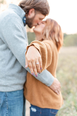 Engagement Photos Al Sabo Land Preserve Kalamazoo Michigan Open Field cute couple kissing showing engagement ring hand