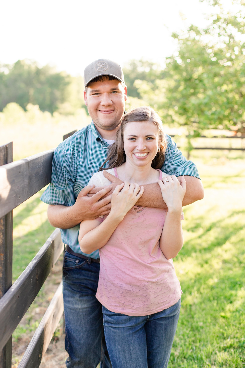 engaged couple hugging by fence line Something Blue Berry Farm Wedding Venue
