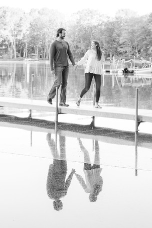 cute couple engagement photos walking on lake dock reflection in water