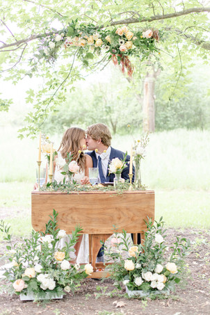 bride and groom kissing sweetheart table reception in the details byron center truer design