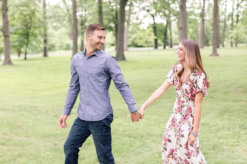engaged cute couple walking laughing at the Rivere Park Midland Michigan