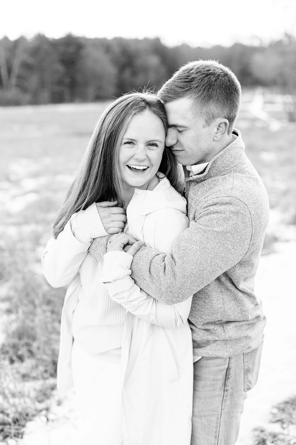 Josh and Andrea wedding photography husband and wife team michigan engagement session Al sabo land preserve couple laughing standing in snowy field