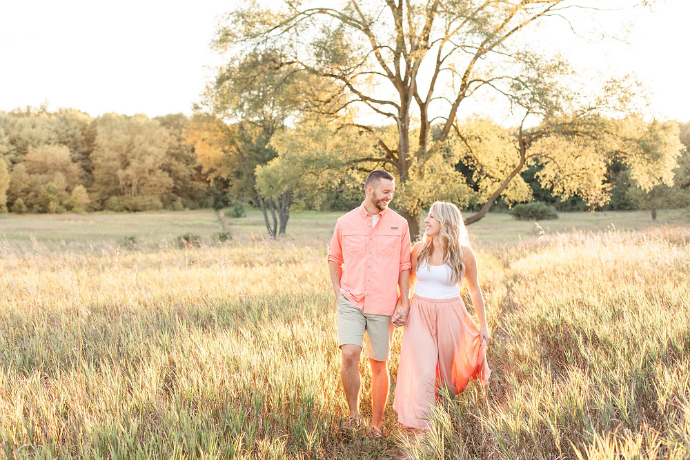 Engagement Photos Al Sabo Land Preserve Kalamazoo Michigan couple walking in Open Field