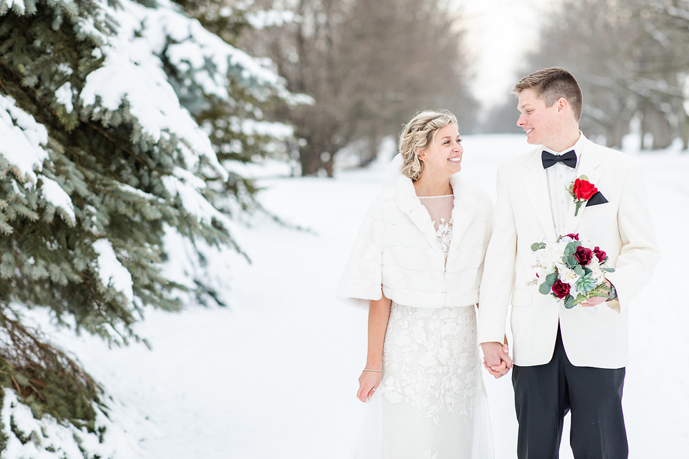 josh and Andrea photography husband and wife team michigan winter wedding south haven bride and groom standing smiling holding hands
