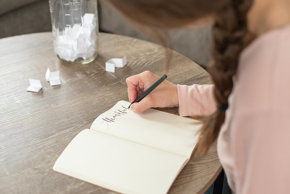 girl writing thankful table book