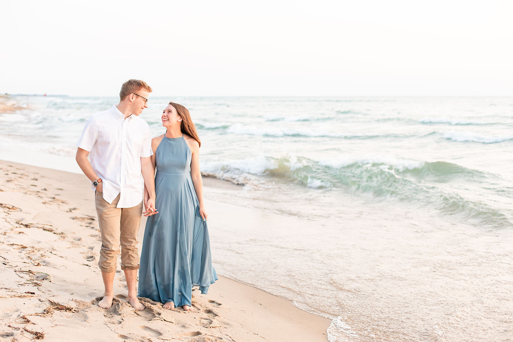 Engagement Photos Tunnel Park Beach Holland Michigan Engaged Couple holding hands standing by water