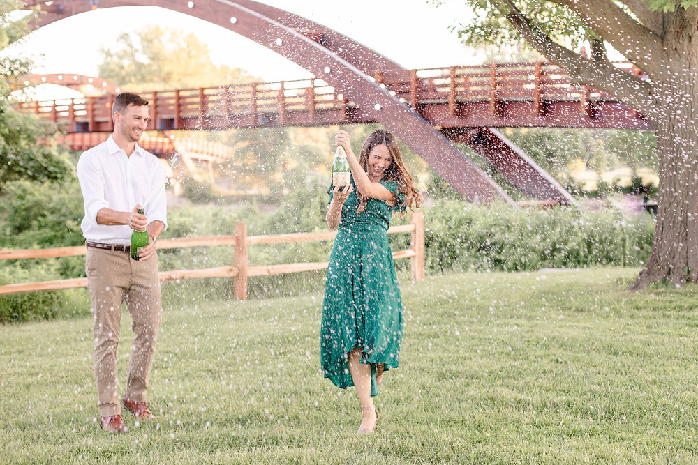 engaged couple popping champagne bottle in front of The Tridge Midland Michigan