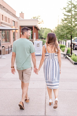 engaged cute couple walking downtown Midland Michigan