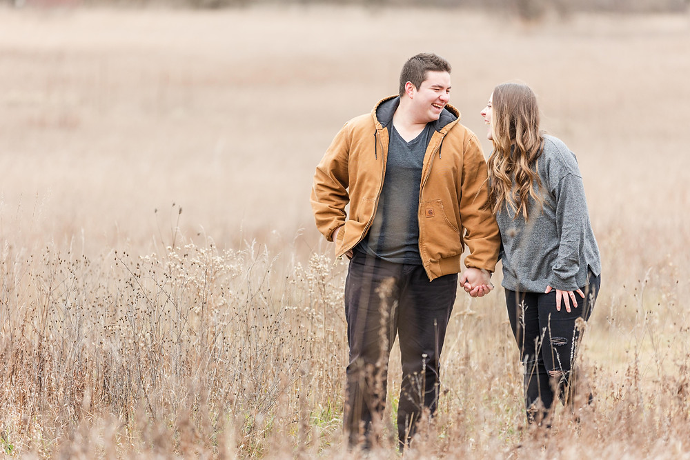josh and Andrea photography husband and wife team michigan engagement photo shoot al sabo land preserve man and woman laughing standing in field