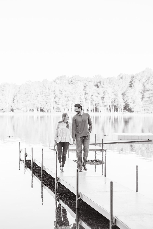 cute couple engagement photos walking on lake dock