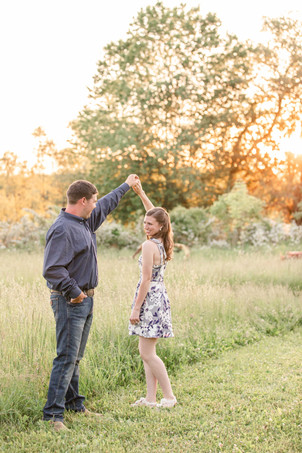 engaged couple twirling dancing open grassy field Something Blue Berry Farm Wedding Venue