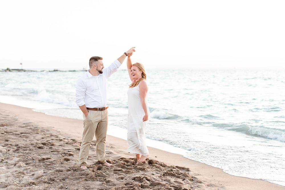 engagement photos cute couple twirling on city beach new buffalo michigan white dress