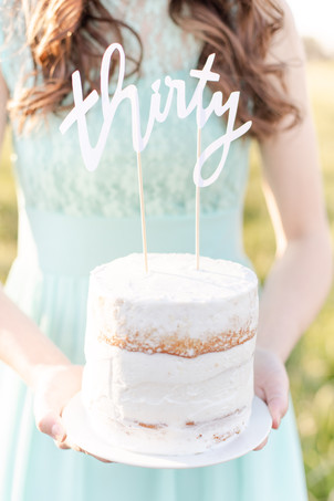 pretty woman in field at sunset holding cake