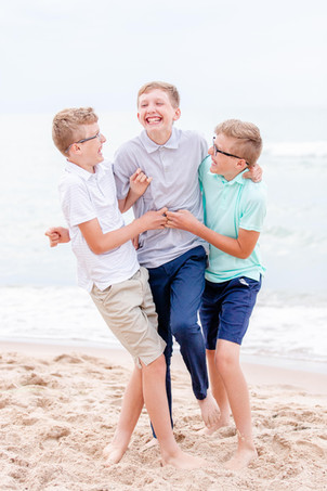 three teen boys laughing on beach Lake Michigan South Haven Michigan