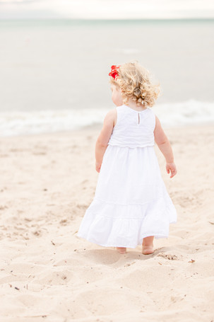 little girl blond curls walking on the beach Lake Michigan south haven family shoot
