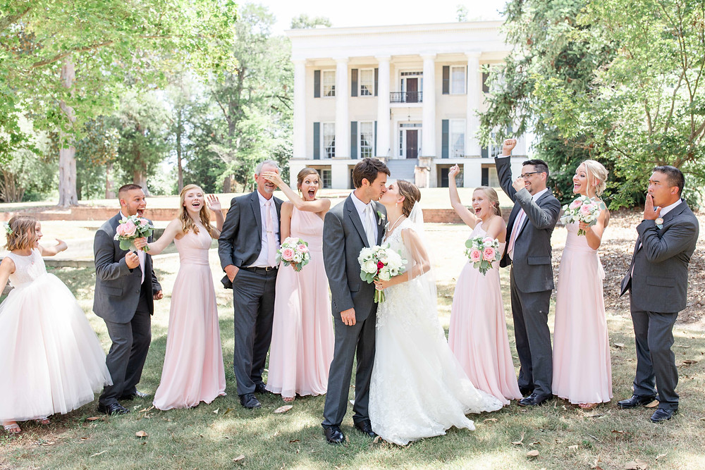 Bride and Groom kissing bridal party cheering Rose Hill Antebellum Lockerly Arboretum Milledgeville Georgia Wedding