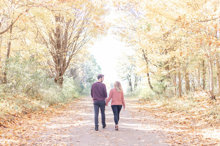 man and woman walking down a road with trees and fall colors