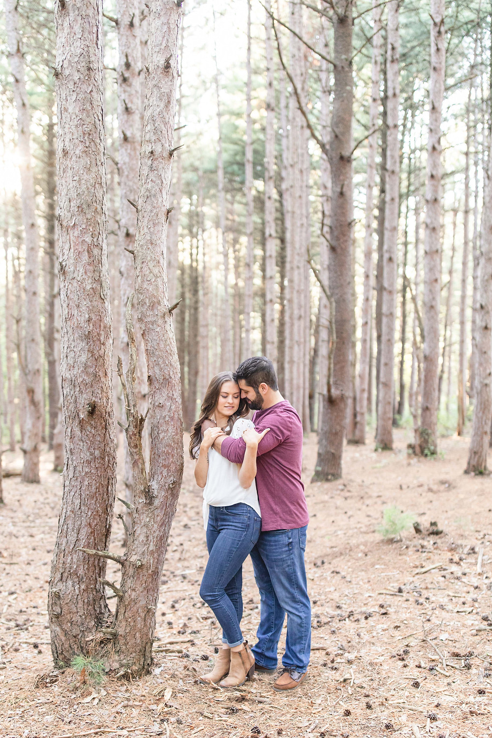 Cute couple standing woods provin trails Grand Rapids engagement session