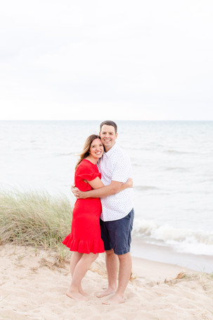 cute couple on the beach hugging Lake Michigan south haven family shoot