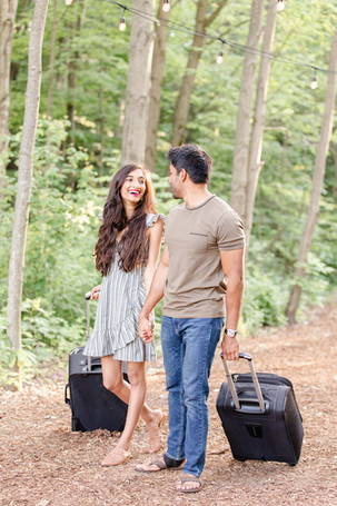 couple rolling suitcases in forest The Fields of Michigan South Haven luxury glamping experience