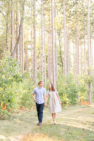 Engagement Photos Riley Trails Holland Michigan Engaged Couple walking holding hands smiling