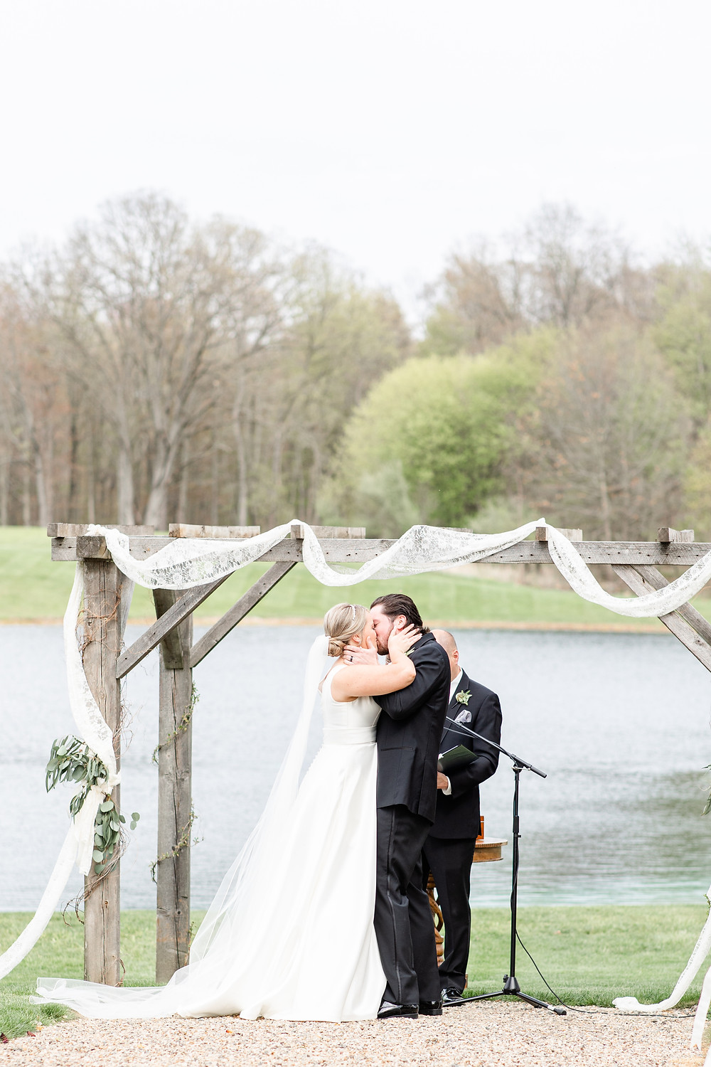Josh and Andrea wedding photography husband and wife photographer team michigan Black Barn Wedding Venue rives junction spring bride and groom first kiss ceremony